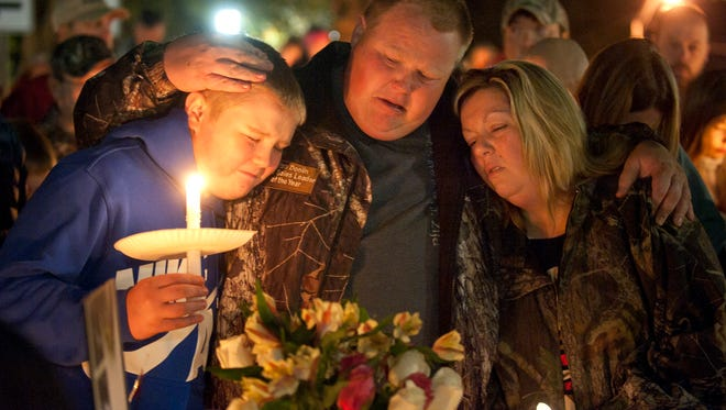 Gabriella Doolin's brother Alec, father Brian and mother Amy, comfort each other during a vigil for her Sunday, Nov. 15, 2015, in Scottsville, Kentucky. The body of Gabriella, 7, was found in a creek in a wooded area behind Allen County-Scottsville High School on Saturday evening, according to a news release from Kentucky State Police Post 3 in Bowling Green, Kentucky. Her death is being investigated by KSP detectives as a homicide.