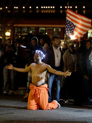 A man kneels in the middle of a street and yells at police before being arrested outside the Ferguson Police Department Saturday, Nov. 29, 2014, in Ferguson, Mo.