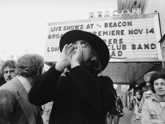 John Lennon poses in front of the marquee of New York's