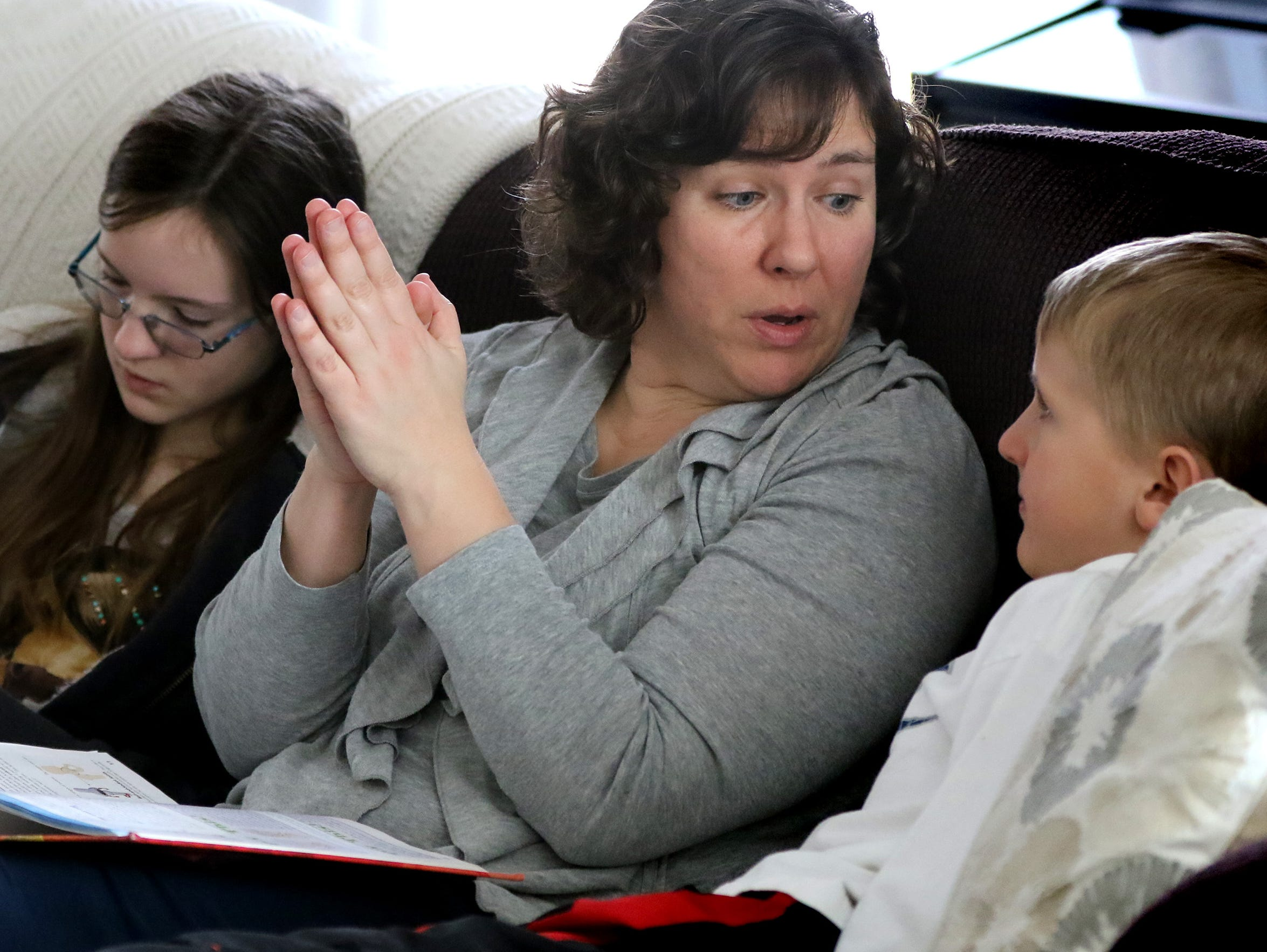 Colleen Boehm and her children Ellie, 12, and Nick, 9, gather on a living room couch to read through a section on bone structure and joints for a unit on human anatomy at their Sussex home on March 28.