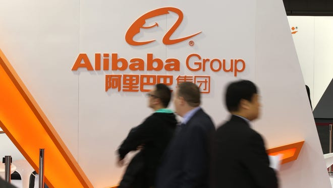 Exhibition visitors walk past the exhibition booth of the Alibaba Group at the CeBIT 2015 international computer expo in Hanover, Germany