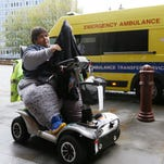 Kevin Chenais puts on his jacket as he sits in his mobility scooter in front of an ambulance at St Pancras in London on Nov. 20, 2013.