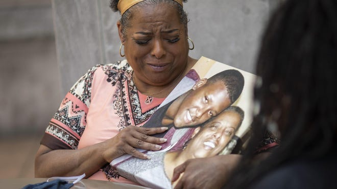 While holding a photo of her son, Maquita Tolliver talks about the unsolved murder of Miles Tolliver, who was shot and killed on Jan. 26, during a press conference with her daughter, Candice Tolliver, right, and Columbus Division of Police detective Scott Polgar, not pictured, outside Linden-McKinley High School on Thursday, Aug. 13, 2020.