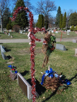 An evergreen arrangement hangs from a shepherd's hook at Lakeside Cemetery. People with loved ones at the cemetery must remove decorations no later than March 31.