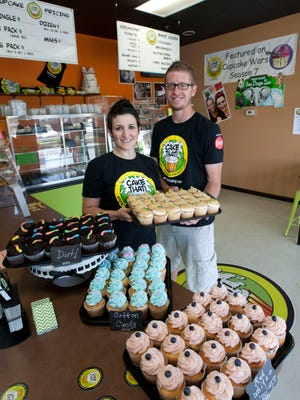 Jessica Bartlett stands with her husband, Bob, in their Stafford store, Cake That!