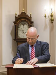 Gov. Jack Markell signs bills into law Friday morning in Dover. The legislative session ended following a marathon meeting that lasted into the early morning hours.