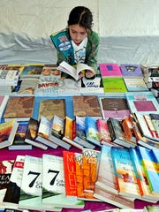 McKinzie Davis, 10, takes a look at books at the Baker Publishing Group tent during the Southern Festival of Books in 2012.