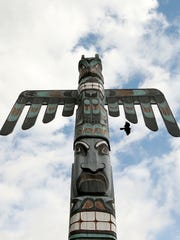 A crow soars past the totem at Manette Plaza on Wednesday.