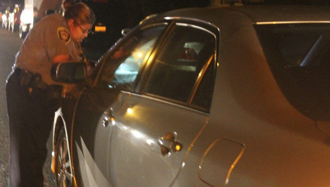 Maria Celis, traffic service assistant with the Oxnard Police Department, writes down the vehicle identification number of a car that has been left running unattended during a traffic enforcement operation.