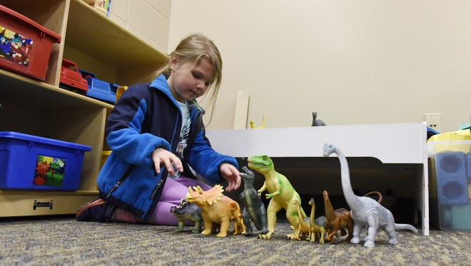 Marley Nelson, 4 checks out the dinosaurs during an open house Thursday for Learning Adventures preschool at Harvey Dunn Elementary School, April 7, 2016.
