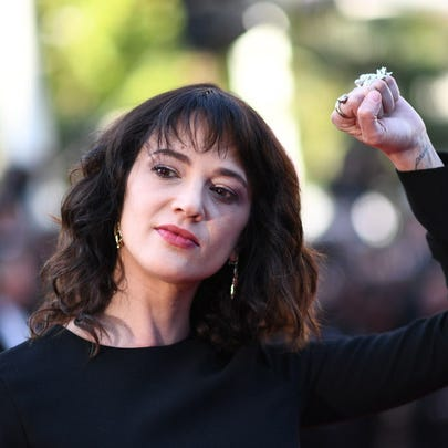Actress Asia Argento raises her fist as she arrives