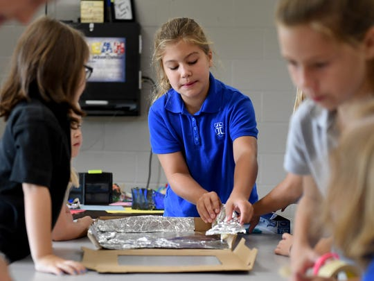 Jackson Christian 4th grader Graesyn Jones helps kindergartners in creating a solar oven during class, Monday, Aug. 21. The students are learning about the solar eclipse and how the sun works.