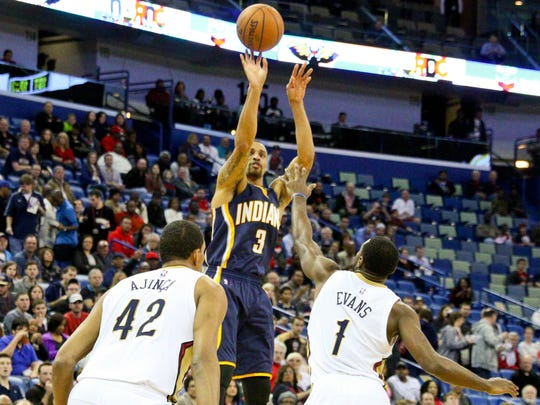 Pacers guard George Hill (3) shoots over New Orleans Pelicans guard Tyreke Evans (1) and center Alexis Ajinca (42) during the first half of a game at the Smoothie King Center. The Pacers defeated the Pelicans 106-93.