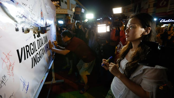 Kelly Wen, wife of a Chinese passenger onboard the missing Malaysia Airlines Flight MH370 looks at an airplane poster during an event to mark one year anniversary of the pane disappearance in Kuala Lumpur, Malaysia, on March 6, 2015.