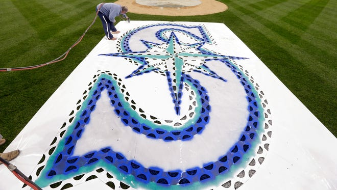 Seattle Mariners' head groundskeeper Bob Christofferson paints on a team logo stencil behind home plate in preparation for the new season Wednesday, April 1, 2015, in Seattle. The Mariners open at home against the Los Angeles Angles Monday, April 6.