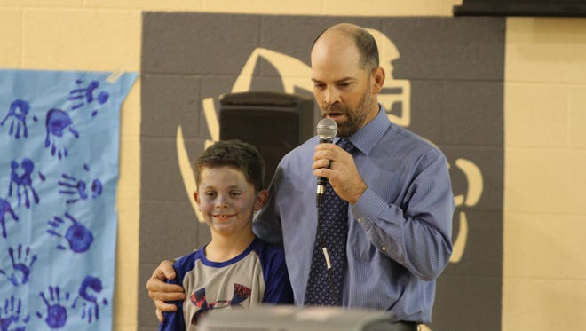 Davis Principal Jeff Kirby opens the Blue Ribbon Award ceremony by introducing a student who painted his face blue in honor of Grinnell's Davis Elementary being designated a National Blue Ribbon School.