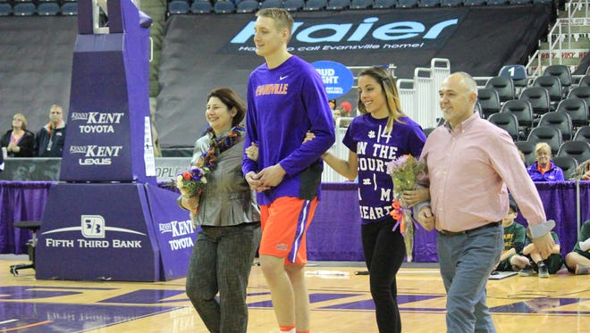 Evansville men's basketball player Sergej Vucetic is escorted by (from left) Jasna Hamzic, Jelena Merseli and Maid Hamzic during Senior Day ceremonies before the Aces' game against Indiana State on Feb. 25.