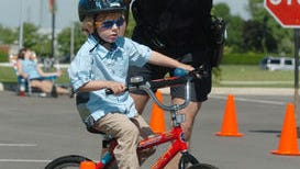 West Chester Police officer shows Jack Missman,5 of Mason through the cone course in the parking lot of the West Chester Library where the West Chester Police Department hosts a bike rodeo complete with safety check and safety guidelines.The Enquirer/ Tony Jones