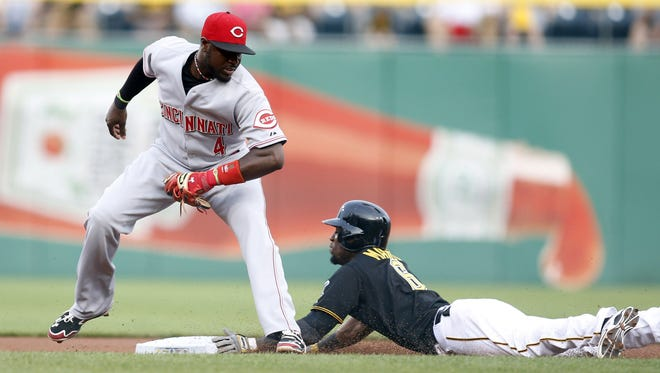 Pittsburgh Pirates left fielder Starling Marte (right) steals second base before Cincinnati Reds second baseman Brandon Phillips (4) can apply the tag during the first inning at PNC Park.