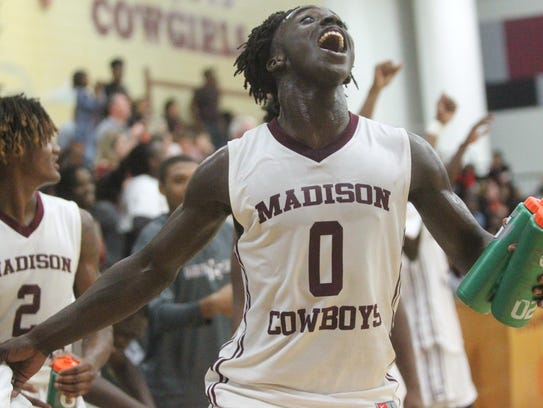 Madison County point guard Travis Jay celebrates a