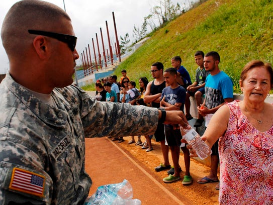 An Army serviceman gives bottled water to residents