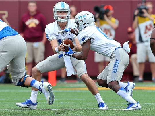 MTSU quarterback John Urzua hands off to Ty Lee in a game against Minnesota at TCF Bank Stadium on Sept. 16, 2017.