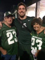 MSU senior linebacker Chris Frey Jr. takes a post-game photo with his grandparents, Clarence and Kaye Smith, in East Lansing.