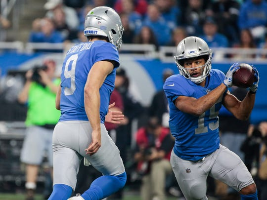 Lions quarterback Matthew Stafford, left, flips the ball to receiver Golden Tate in the second half against the Vikings at Ford Field, Thursday, Nov. 23, 2017.