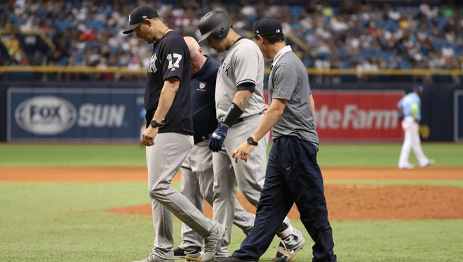 Yankees catcher Gary Sanchez walks off the field with manager Aaron Boone and trainer as he leaves Sunday's game with an groin injury.