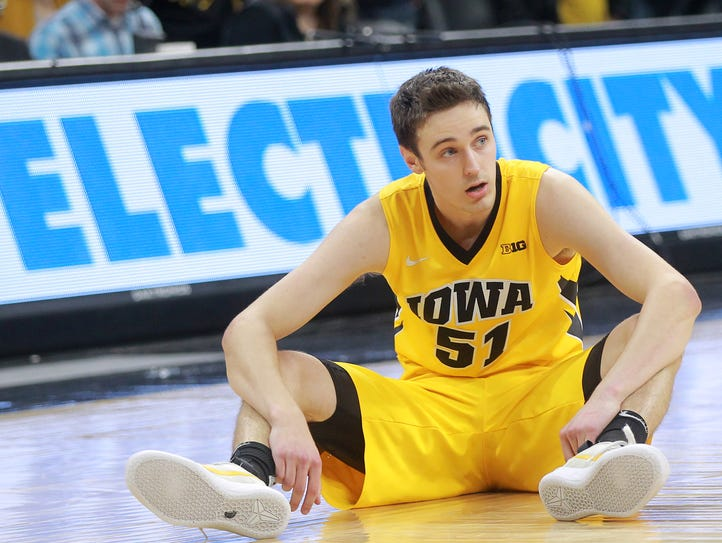 Iowa's Nicholas Baer sits on the court after the Hawkeyes'