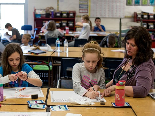 Third-grade teacher Patti Lowhorn works with Kadence Dunn and Kaylee Ketelhut, both 8, Thursday, Feb. 23, 2017 at Palms Elementary School in Ira Township.