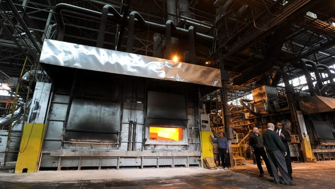In this file photo, an employee of Skana Aluminum Co. opens their melting furnace.