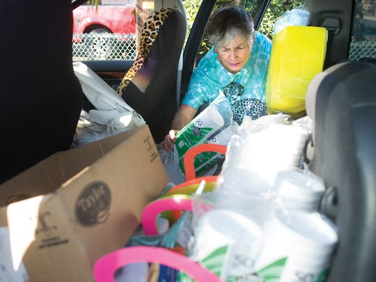 Donna Johnson takes out plastic silverware and paper plates from her vehicle as she delivers bottles of water Jan. 30 in East Porterville.
