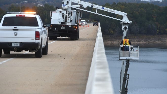 An engineer with the Arkansas State Highway and Transportation Department works Wednesday inspecting the U.S. Highway 62 Veterans Memorial Bridge over Norfork Lake.