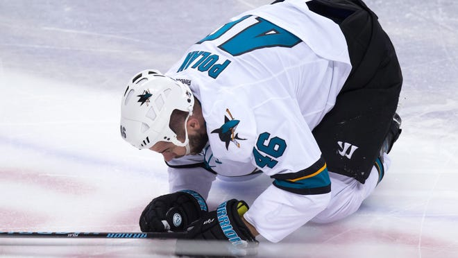 San Jose Sharks' Roman Polak kneels on the ice after being hit by Vancouver Canucks' Jake Virtanen.