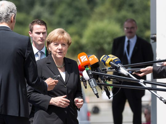 German Chancellor Angela Merkel, center, speaks with the press as she arrives for an European People's Party meeting in Kortrijk, Belgium on Thursday, June 26, 2014. European Union heads of state will gather on Thursday for the first day of an EU summit in the city Ypres and will participate in a ceremony to commemorate the outbreak of World War I under the Menin Gate.  (AP Photo/Thierry Monasse)