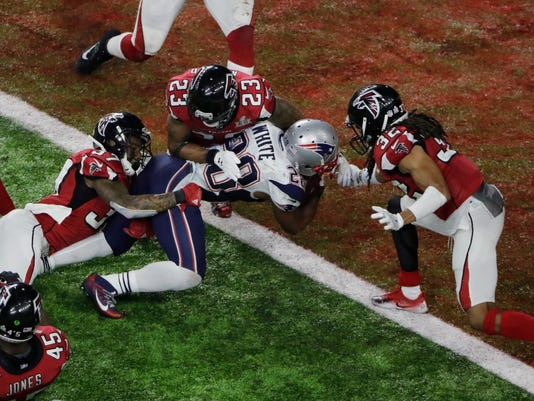 FILE - In this Feb. 5, 2017, file photo, New England Patriots' James White scores the winning touchdown during overtime of the NFL Super Bowl 51 football game against the Atlanta Falcons, in Houston.  The Falcons and Patriots have lived in two different realities since their Super Bowl matchup in February. New England has savored the memories of how it turned a 25-point second-half deficit into largest comeback victory in Super Bowl history. Meanwhile, Atlanta has had to live through a constant stream of internet memes and endless jokes about the seemingly insurmountable lead it let slip away.(AP Photo/Charlie Riedel, File)