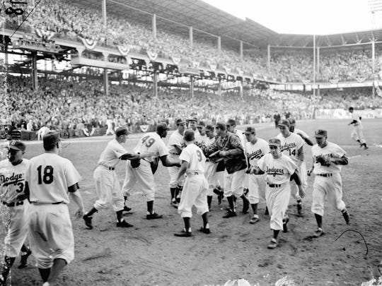 Dodger players rush to congratulate Carl Erskine, fourth from right, after he completed a very brilliant pitching job against the Yankees in the third game of the World Series at Ebbets Field in Brooklyn, N.Y., on October 2, 1953.  Erskine held the Yankees to six hits, struck out 14 for an all-time series record, and won the game 3-2.  Dodgers are, from left to right:  George Shuba, Joe Black (49), Erv Palica, Don Zimmer (9), coach Cookie Lavagetto, background, Dick Williams, Erskine, Preacher Roe, Wayne Belardi, Bill Antonello, bat boy, Gil Hodges, Jackie Robinson, rear, and Pee Wee Reese.