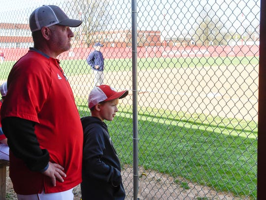 Bosse High School baseball head coach Craig Shoobridge in the dugout with his 10 year-old son Luke during a game with Castle High Thursday, April 19, 2018.