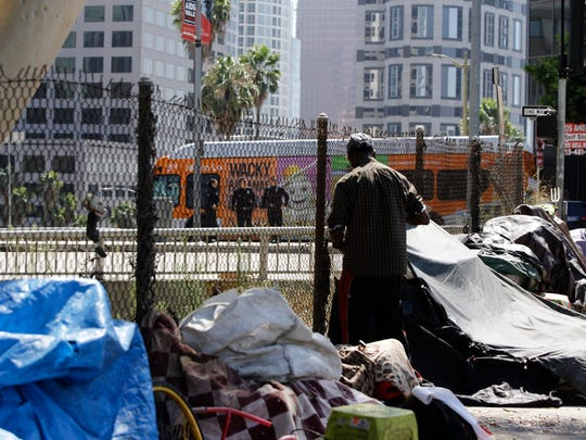 "A man adjusts his spot in a newly displaced homeless camp while Los Angeles police officers guard a Harbor Freeway ramp during the visit of President Donald Trump to Los Angeles on Tuesday. Trump said he will do ""something"" about homelessness but offered no specifics beyond the mention of creating a task force."
