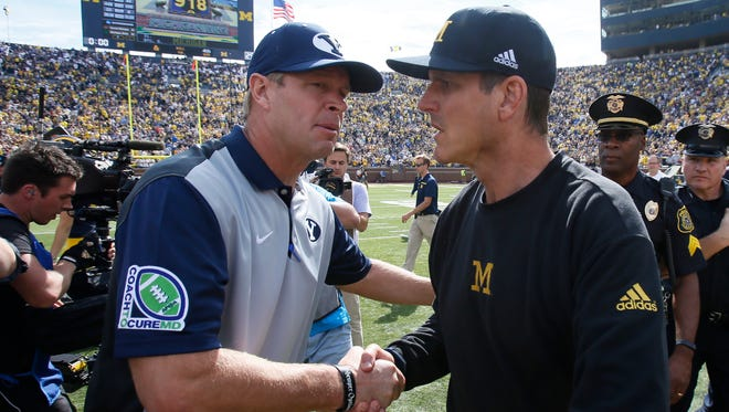 Brigham Young University head coach Bronco Mendenhall shakes hands with Michigan head coach Jim Harbaugh after Michigan's 31-0 win in their football game on Saturday, September 26, 2015, in Ann Arbor. Julian H. Gonzalez/Detroit Free Press