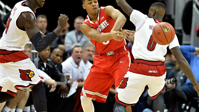 Ohio State guard D'Angelo Russell, center, makes a pass around Louisville's Terry Rozier during the first half Tuesday night in Louisville, Ky. At left is Louisville's Montrezl Harrell.