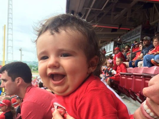 Lynn Ratcliff's son's baby, George Edgar, named after grandpa, at his first Reds game sitting next to his dad, Joe.