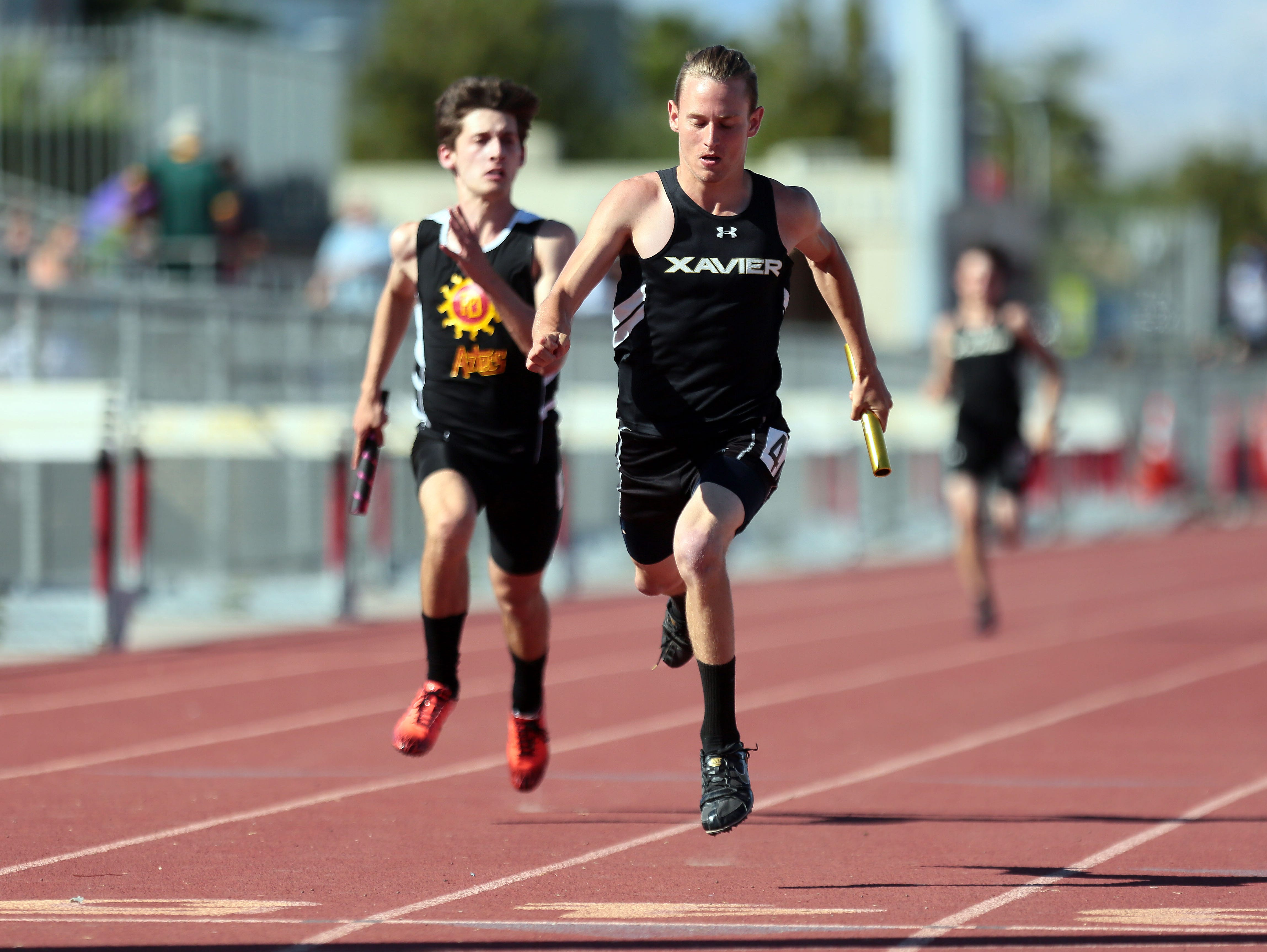 Xavier's Chris McElrath beats out Palm Desert's Spencer Platamore to win for his relay team during a track meet at Palm Desert High on Thursday, March 24, 2016