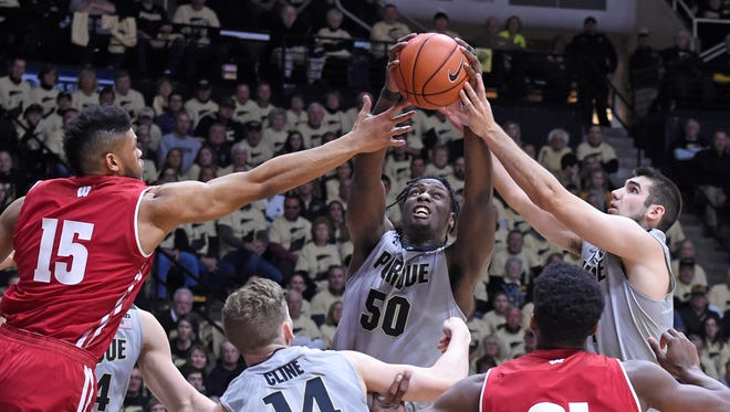 Purdue's Caleb Swanigan (50) and Dakota Mathias (31) go for a rebound over the outstretched arm of Wisconsin's Charles Thomas IV.