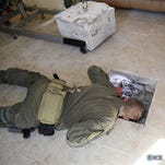 This photo provided by U.S. Immigration and Customs Enforcement shows an investigator Wednesday, March 23, 2016, peering into a tunnel at a newly-built home in Calexico, Calif., that runs the length of four football fields to a restaurant in Mexicali, Mexico.