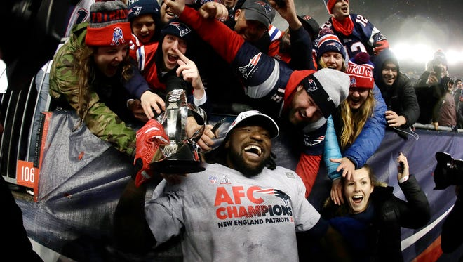 New England Patriots running back LeGarrette Blount holds the AFC championship trophy surrounded by fans after the AFC championship NFL football game, Sunday, Jan. 22, 2017, in Foxborough, Mass. The Patriots defeated the the Pittsburgh Steelers 36-17 to advance to the Super Bowl.