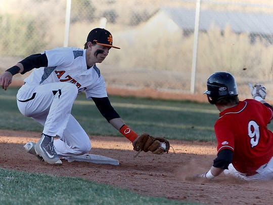 Aztec's Jake Taylor tags out Albuquerque Academy's Seth Jones at second base during their game on April 1 in Aztec.