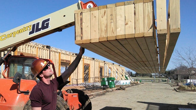 This three-story, 16-unit apartment building with retail space and underground parking is one of several North Liberty construction projects now in full swing.  Kalvin Hodge of Hodge Carpentry is shown examining a set of floor joists this week at the site along West Penn Street.