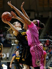 Torrie Thornton drapes her arms over Ally Disterhoft of Iowa Sunday, January 24, 2016, at Mackey Arena. Purdue defeated Iowa 90-73.